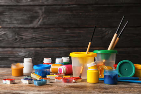 Set of child painting materials on table near wooden wall. Space for text 写真素材