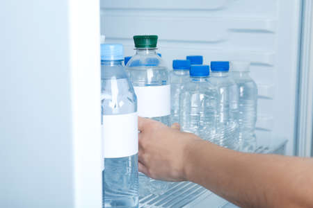 Woman taking bottle of water from refrigerator, closeup. Mockup for design