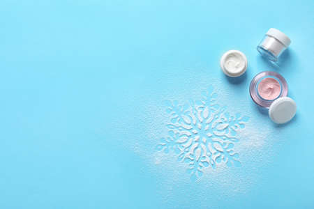 Set of cosmetic products on blue background, flat lay with space for text. Winter care