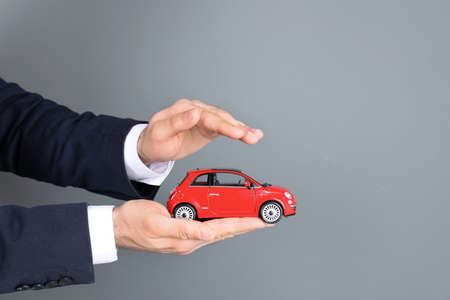 Male insurance agent holding toy car on grey background, closeup. Space for text Reklamní fotografie