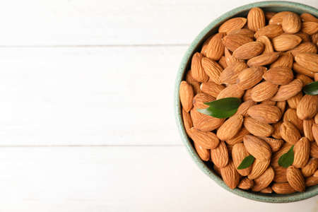 Tasty organic almond nuts in bowl and space for text on table, top view Archivio Fotografico