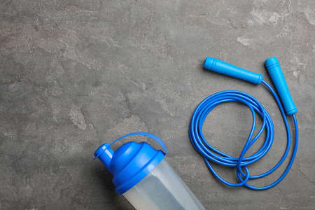 Jump rope, bottle of water and space for text on grey background, top view Stock Photo