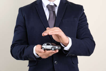Male insurance agent holding toy car on light background, closeup