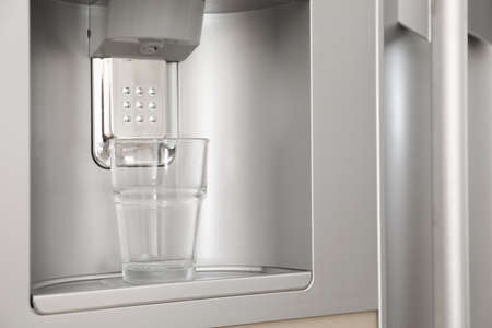 Refrigerator with ice and water system, closeup. Modern kitchen appliance
