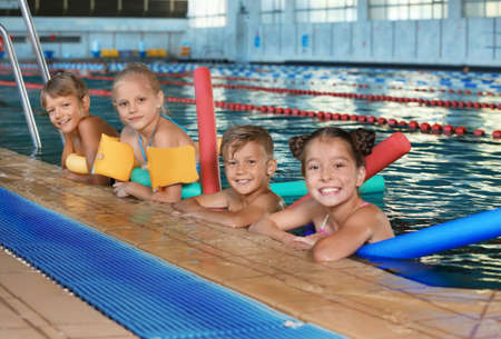 Little kids with swimming noodles in indoor pool