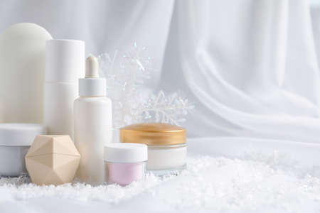 Set of cosmetic products and decorative snow on white fabric, space for text. Winter care