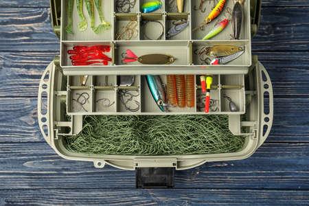 Boîte avec différents accessoires de pêche sur fond en bois, vue de dessus Banque d'images