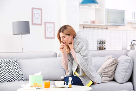 Woman suffering from cough and cold on sofa at home Standard-Bild - 112036804