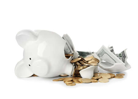 Broken piggy bank with money isolated on white background