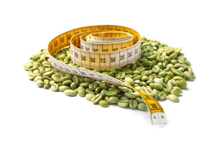 Pile of green coffee beans and measuring tape on white background
