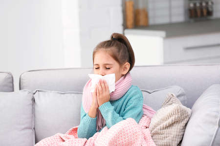 Little girl suffering from cough and cold on sofa at home 版權商用圖片