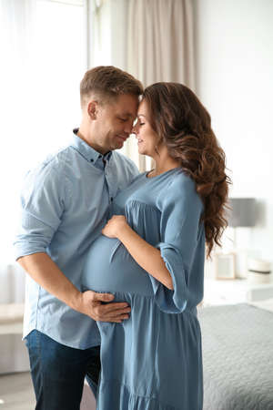 Pregnant woman with her husband in bedroom. Happy young family Standard-Bild