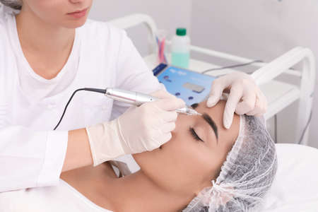 Young woman undergoing procedure of permanent eyebrow makeup in tattoo salon Stock Photo