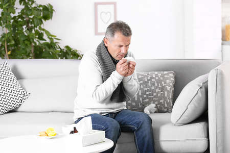 Man suffering from cough and cold on sofa at home