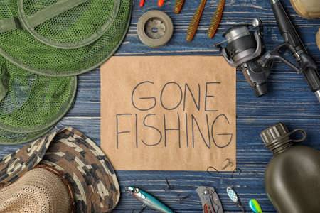 Flat lay composition of angling equipment and paper with words GONE FISHING on wooden background