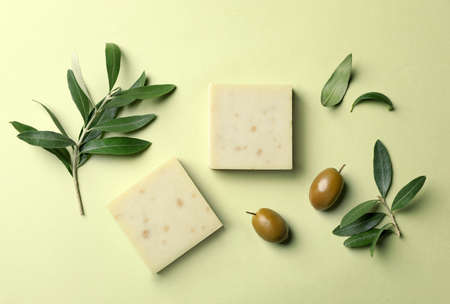 Handmade soap bars and leaves with olives on color background, top view