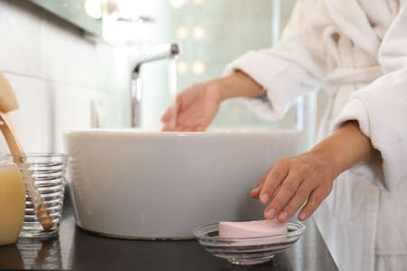 Young woman taking soap bar to wash hands in bathroom, closeup