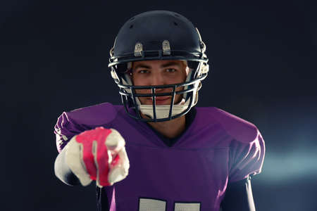 American football player in uniform on dark background
