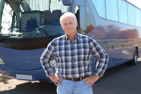 Professional driver standing near bus. Passenger transportation Stock Photo