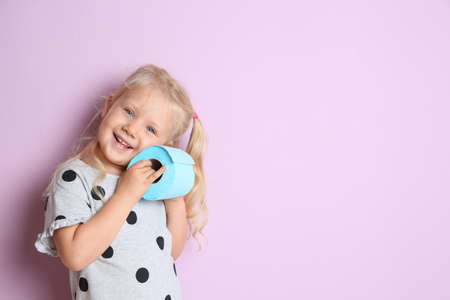 Cute little girl holding toilet paper roll on color background. Space for text