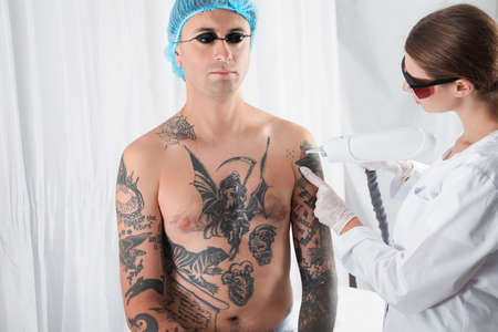 Man undergoing laser tattoo removal procedure in salon Banque d'images - 112040961