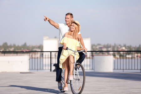 Happy couple riding bicycle outdoors on sunny day