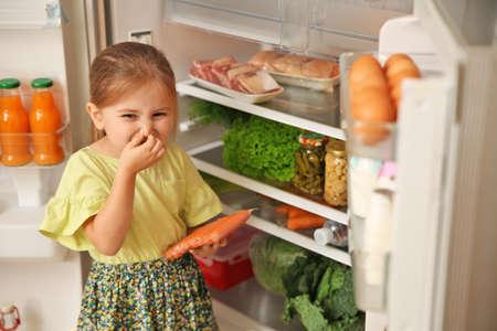 Niña linda con salchichas que huelen mal cerca del refrigerador en casa
