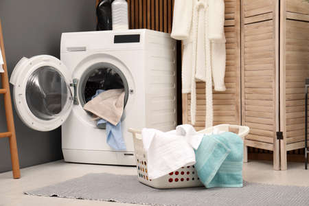 Basket with dirty towels on washing machine in modern laundry room