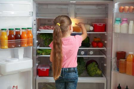 Cute little girl choosing food in refrigerator at home Banco de Imagens