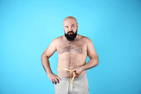 Fat man with measuring tape on color background. Weight loss
