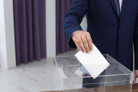 Man putting his vote into ballot box at polling station, closeup. Space for text