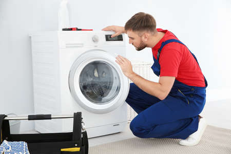 Young plumber examining washing machine in bathroom