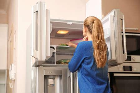 Jonge vrouw die thuis voedsel in de koelkast kiest Stockfoto