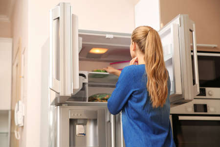 Young woman choosing food in refrigerator at home