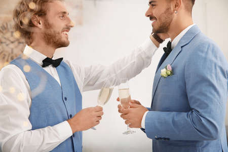 Happy newlywed couple with glasses of champagne at home