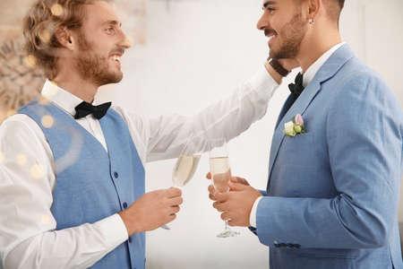 Heureux couple de jeunes mariés avec des verres de champagne à la maison
