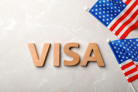Flat lay composition with word VISA and flags of USA on gray background