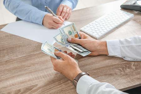 Man with money at cash department, closeup