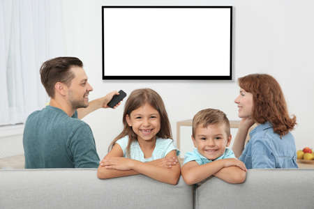 Family with remote control sitting on couch and watching TV at home, space for design on screen. Leisure and entertainment