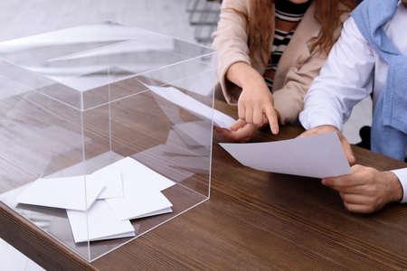 Wahllokalmitarbeiter am Tisch mit Wahlurne