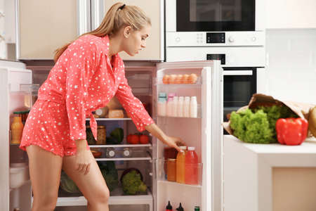 Beautiful young woman choosing food in refrigerator at home
