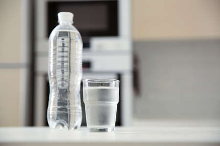 Glass and plastic bottle with water on table in kitchen. Space for text