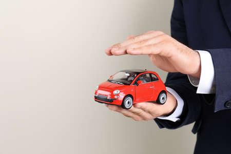 Männlicher Versicherungsvertreter mit Spielzeugauto auf hellem Hintergrund, Nahaufnahme. Platz für Text