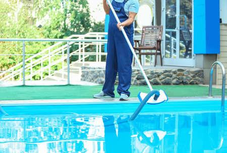 Trabajador masculino limpieza piscina exterior con aspiradora subacuática