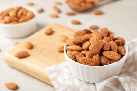 Wooden board with tasty organic almond nuts in bowl on table. Space for text