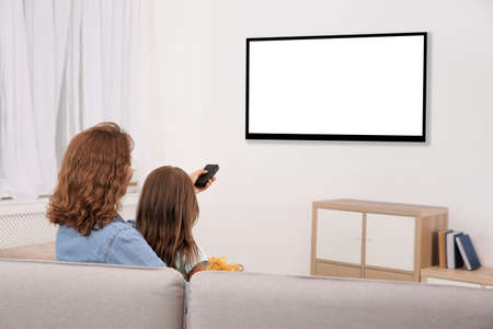 Mother and daughter with remote control sitting on couch and watching TV at home, space for design on screen. Leisure and entertainment