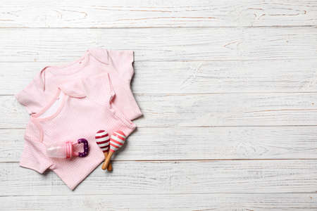 Flat lay composition with baby clothes and accessories on wooden background. Space for text