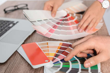 Team of designers working with color palettes at office table, closeup