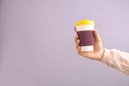 Woman holding takeaway paper coffee cup on color background. Space for text