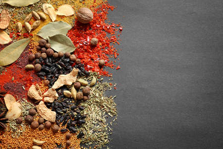 Different aromatic spices on dark background, top view with space for text